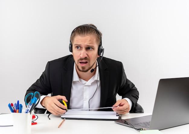 Hübscher geschäftsmann im anzug und in den kopfhörern mit einem mikrofon, das verwirrt beiseite am tisch in offise über weißem hintergrund sitzt