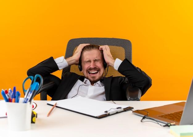Hübscher geschäftsmann im anzug und in den kopfhörern mit einem mikrofon, das wild geht, indem er sein haar zieht, das am tisch in offise über orange hintergrund sitzt