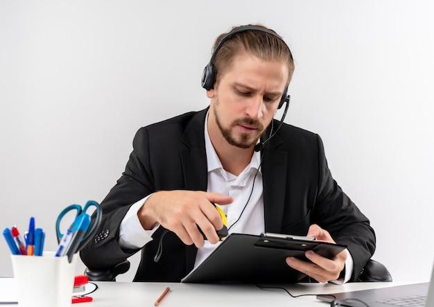 Hübscher geschäftsmann im anzug und in den kopfhörern mit einem mikrofon, das zwischenablage hält, die es mit ernstem gesicht betrachtet, das am tisch in offise über weißem hintergrund sitzt