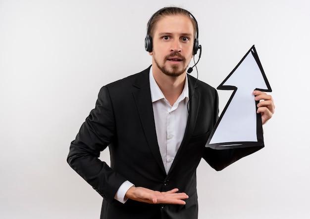 Hübscher geschäftsmann im anzug und in den kopfhörern mit einem mikrofon, der weißen pfeil hält, der kamera verwirrt über weißem hintergrund stehend betrachtet