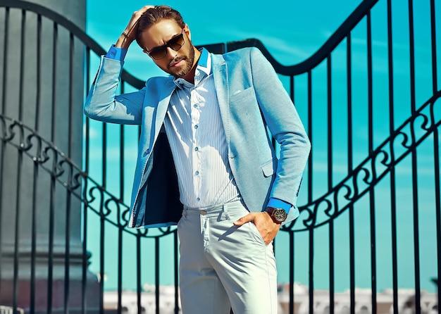 Hübscher geschäftsmann im blauen anzug in der straße, die sonnenbrille trägt