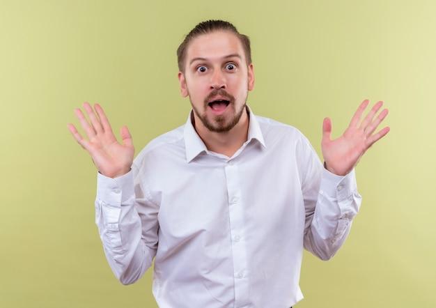 Hübscher geschäftsmann im weißen hemd, das kamera betrachtet, die hände in der übergabe erhebt, die erstaunt steht über olivenhintergrund Kostenlose Fotos