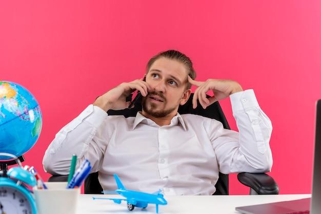 Hübscher geschäftsmann im weißen hemd, das müde und gelangweilt am handy spricht, sitzt am tisch in offise über rosa hintergrund