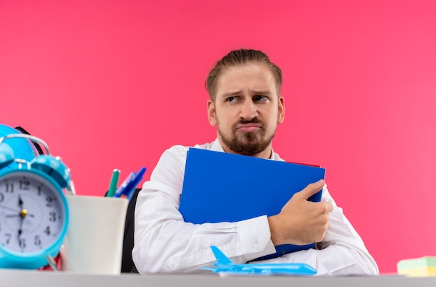 Hübscher geschäftsmann im weißen hemd, der ordner hält, der beiseite mit traurigem ausdruck sitzt, der am tisch in offise über rosa hintergrund sitzt