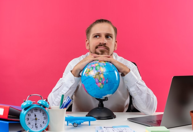 Hübscher geschäftsmann im weißen hemd mit dem globus, der beiseite schaut verwirrt am tisch in offise über rosa hintergrund schaut