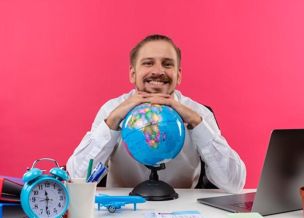 Hübscher geschäftsmann im weißen hemd mit globus, der kamera mit lächeln auf gesicht betrachtet, das am tisch in offise über rosa hintergrund sitzt