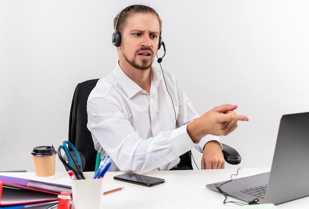 Hübscher geschäftsmann im weißen hemd und in den kopfhörern mit einem mikrofon, das am laptop arbeitet, verwirrt verwirrt sitzt am tisch in offise über weißem hintergrund
