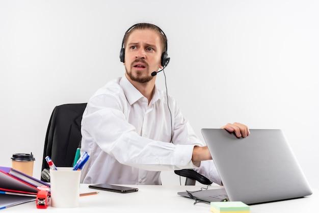 Hübscher geschäftsmann im weißen hemd und in den kopfhörern mit einem mikrofon, das an einem laptop arbeitet, der beiseite mit ernstem gesicht schaut, das am tisch in offise über weißem hintergrund sitzt