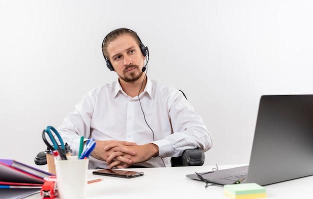 Hübscher geschäftsmann im weißen hemd und in den kopfhörern mit einem mikrofon, das beiseite schaut mit ernstem gesicht, das am tisch in offise über weißem hintergrund sitzt