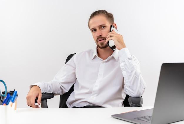 Hübscher geschäftsmann im weißen hemd und in den kopfhörern mit einem mikrofon, das beiseite schaut mit ernstem gesicht, das auf handy spricht, das am tisch in offise über weißem hintergrund sitzt
