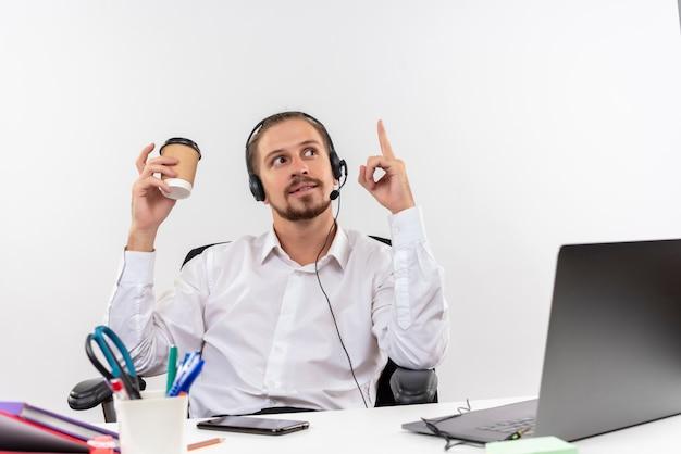 Hübscher geschäftsmann im weißen hemd und in den kopfhörern mit einem mikrofon, das kaffeetasse zeigt, die mit lächelndem finger oben zeigt, der am tisch in offise über weißem hintergrund sitzt