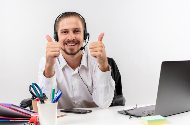 Hübscher geschäftsmann im weißen hemd und in den kopfhörern mit einem mikrofon, das kamera lächelnd zeigt, zeigt daumen hoch, die am tisch in offise über weißem hintergrund sitzen