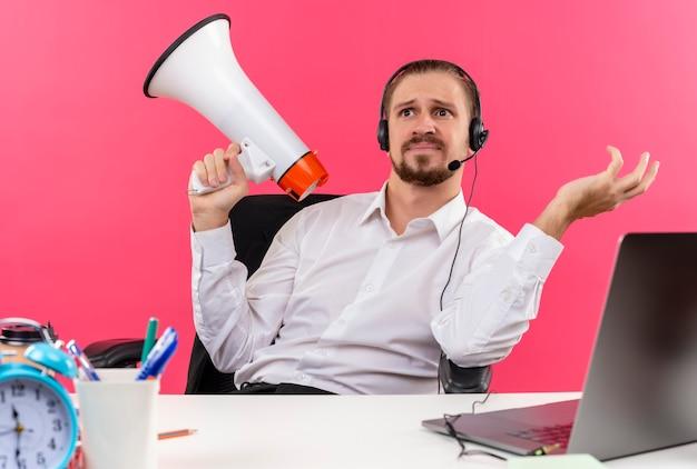 Hübscher geschäftsmann im weißen hemd und in den kopfhörern mit einem mikrofon, das megaphon hält, das verwirrt am tisch in offise über rosa hintergrund sitzt