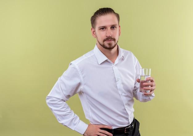 Hübscher geschäftsmann im weißen hemdglas des wassers, das kamera mit dem sicheren ausdruck betrachtet, der über olivenhintergrund steht