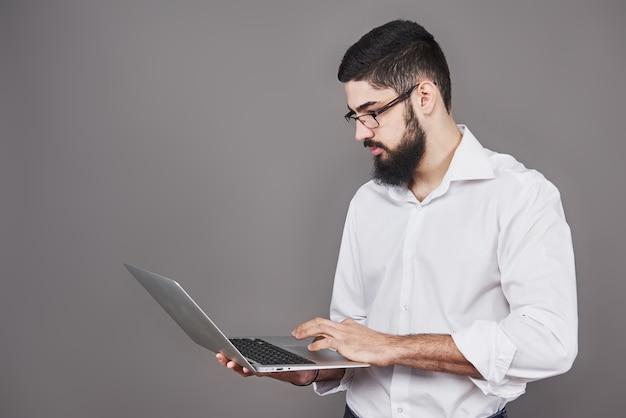 Hübscher geschäftsmann in brille und anzug, der laptop in händen hält und etwas schreibt. seitenansicht. isolierter grauer hintergrund.
