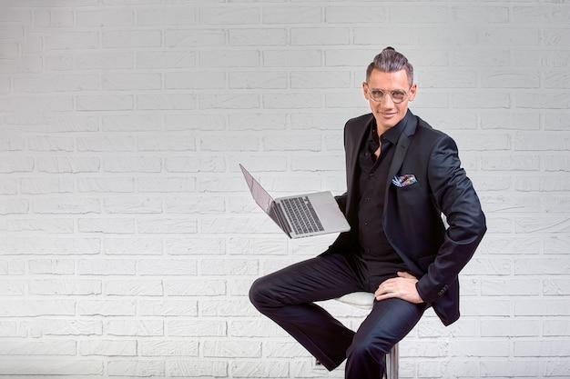 Hübscher geschäftsmann in den gläsern und anzug, die laptop in den händen halten und etwas schreiben.