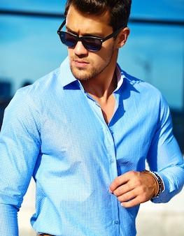 Hübscher geschäftsmann in der formalen kleidung, die in der straße in der sonnenbrille aufwirft