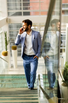Hübscher geschäftsmann in der klage, die am telefon im büro spricht