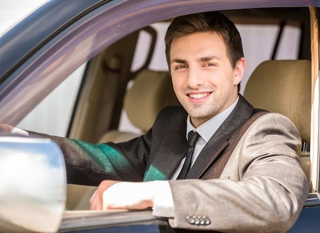 Hübscher geschäftsmann in der klage, die in seinem luxuriösen auto sitzt.