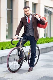 Hübscher geschäftsmann in einer jacke mit roter tasche, die auf seinem fahrrad auf stadtstraßen sitzt.