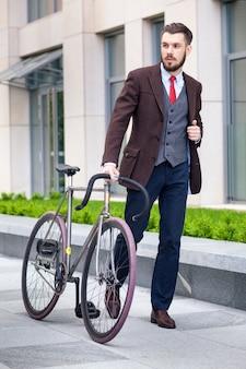 Hübscher geschäftsmann in einer jacke und einer roten krawatte und seinem fahrrad auf den straßen der stadt. das konzept des modernen lebensstils junger männer