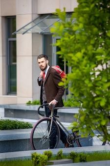Hübscher geschäftsmann in einer jacke und einer roten tasche und seinem fahrrad auf den straßen der stadt. das konzept des modernen lebensstils junger männer