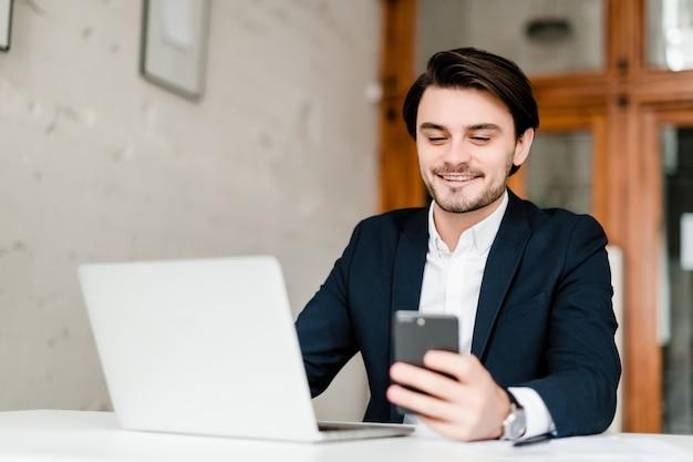 Hübscher geschäftsmann in einer klage benutzt laptop im büro