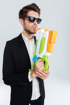 Hübscher geschäftsmann in schwarzer sonnenbrille, der eine bunte wasserpistole über grauer wand hält