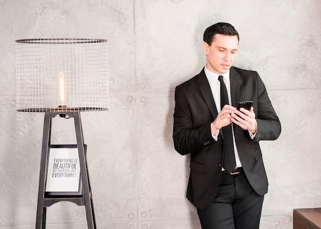 Hübscher geschäftsmann mit dem smartphone, der auf wand sich lehnt