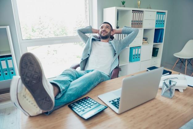 Hübscher geschäftsmann mit einer blauen jacke, die im büro arbeitet