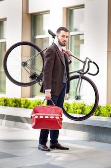Hübscher geschäftsmann mit einer roten tasche, die sein fahrrad auf stadtstraßen trägt. das konzept des modernen lebensstils junger männer