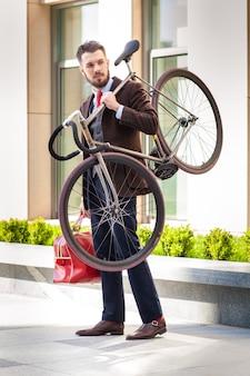 Hübscher geschäftsmann mit einer roten tasche, die sein fahrrad auf stadtstraßen trägt.