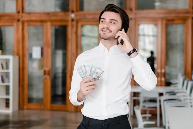 Hübscher geschäftsmann mit geld im büro