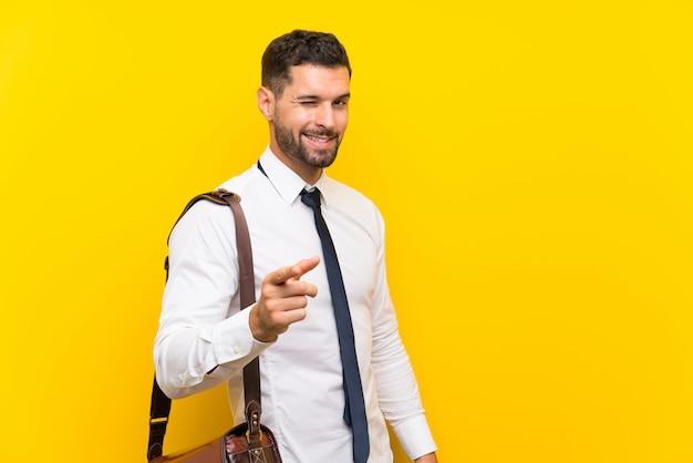 Hübscher geschäftsmann über lokalisiertem gelb zeigt finger auf sie