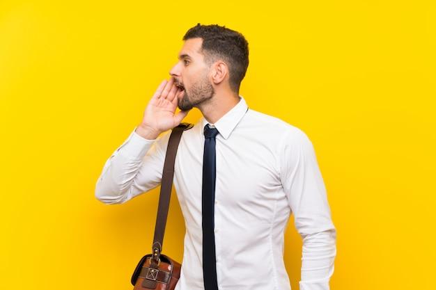 Hübscher geschäftsmann über lokalisierter gelber wand, die mit dem breiten mund schreit, öffnen sich