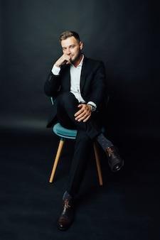 Hübscher geschäftsmannmann, der auf stuhl im fotostudio sitzt