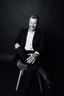 Hübscher geschäftsmannmann mit anzug sitzt auf einem stuhl in einem fotostudio.