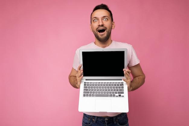Hübscher geschüttelter und überraschter brunet-mann, der laptop-computer hält