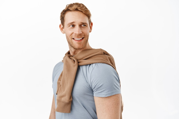 Hübscher gesunder junger mann mit kräftigem körper und roten haaren, kopf nach rechts drehen und zufrieden lächeln, entspannt und sorglos stehen, glückliches und selbstbewusstes gesicht machen, weiße wand