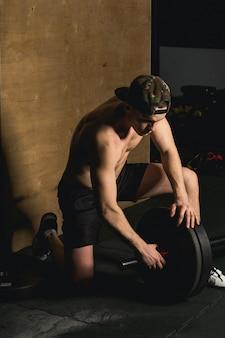 Hübscher gewichtheber, der sich auf das training mit der langhantel vorbereitet