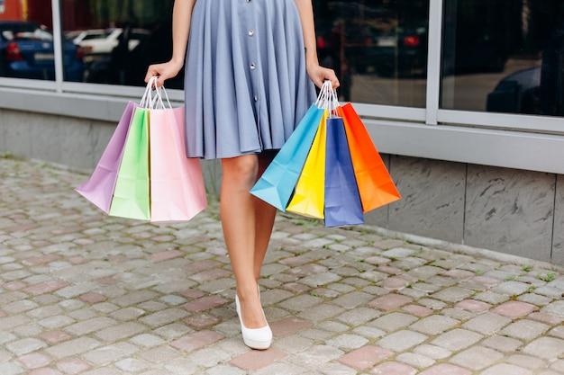 Hübscher girk im kleid, das mehrfarbige einkaufstaschen hält