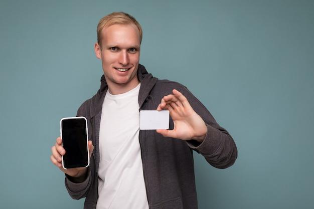 Hübscher glücklich lächelnder blonder mann mit grauem pullover und weißem t-shirt einzeln auf blauer hintergrundwand mit kreditkarte und handy mit leerem bildschirm für mock-up mit blick in die kamera