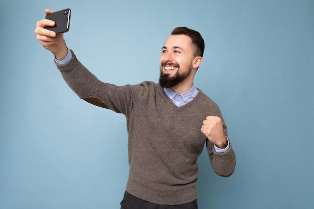 Hübscher, glücklich lächelnder junger mann, der lässige, stilvolle kleidung trägt, die isoliert über der hintergrundwand steht und ein smartphone hält, das ein selfie-foto mit blick auf das bildschirmdisplay des mobiltelefons macht