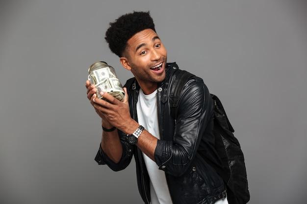 Hübscher glücklicher afroamerikanischer mann in der lederjacke, die bank mit dem geld, beiseite schauend hält