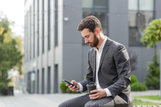 Hübscher, glücklicher bärtiger geschäftsmann, der auf einer bank mit tasse kaffee sitzt außerhalb eines modernen städtischen straßenhintergrundes. stadtpark