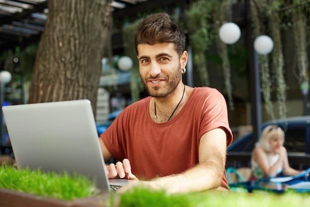 Hübscher glücklicher bärtiger mann in den kopfhörern, der laptop im straßencafé benutzt und fröhlich lächelt