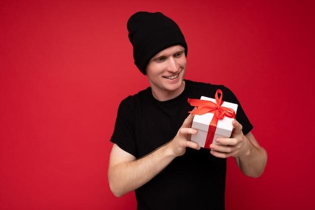 Hübscher, glücklicher, erstaunlicher, amüsanter lächelnder junger mann, der über einer roten hintergrundwand isoliert ist und einen schwarzen hut und ein schwarzes t-shirt trägt, das eine weiße geschenkbox mit rotem band hält und auf die gegenwart schaut