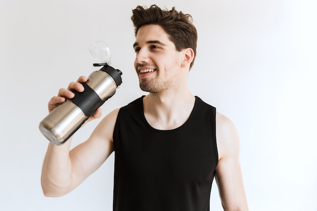 Hübscher glücklicher fröhlicher junger starker sportmann, der wasser aufwirft und trinkt.
