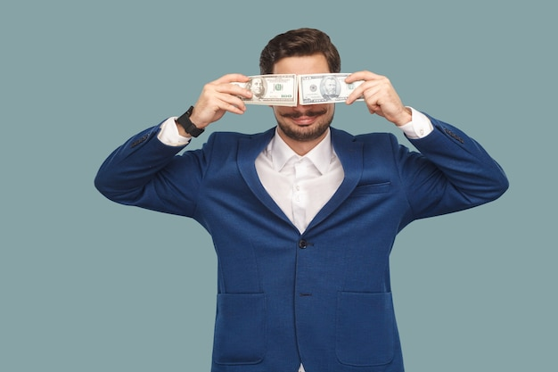 Hübscher glücklicher geschäftsmann in blauer jacke und weißem hemd, der viele dollar vor augen steht und hält und bedeckt und lächelt. innen, studioaufnahme auf hellblauem hintergrund isoliert.