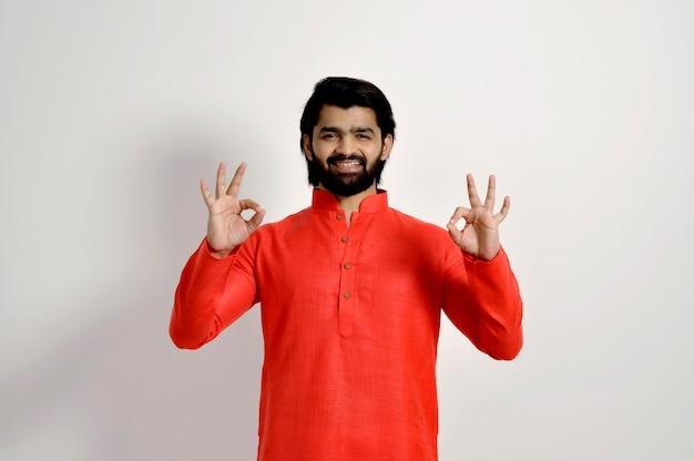 Hübscher glücklicher indischer mann, der kurta trägt, die lächelt und ok zeichen mit beiden händen zeigt